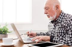 Mature man using laptop and writing in notepad. At home desk. Education, recipe concept Royalty Free Stock Images
