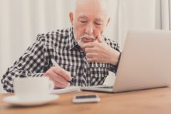 Mature man using laptop and writing in notepad. At home desk. Education, recipe concept stock photography