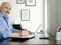 Mature Man Using Laptop And Writing In Notepad. Side view portrait of a mature man using laptop and writing in notepad at home desk Royalty Free Stock Photos