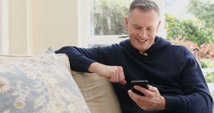 Mature man using mobile phone in living room 4k