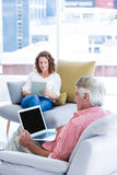 Mature man using notebook while sitting by woman. Mature men using notebook while sitting by women at home Stock Image