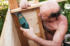 Mature man using power drill building something at contryhouse Royalty Free Stock Photo