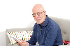 Mature man using a tablet. At home Royalty Free Stock Image