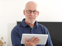 Mature man using a tablet. At home Royalty Free Stock Images