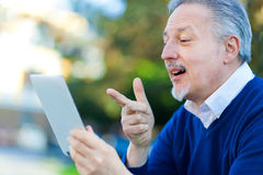 Mature man using a tablet Royalty Free Stock Image
