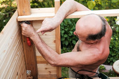 Mature man using tools building structure outside. In summer Royalty Free Stock Images