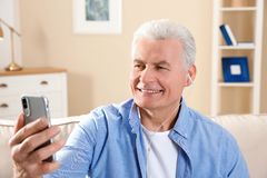 Mature man using video chat on mobile phone royalty free stock photo