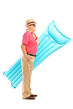 Mature man on vacation holding a swimming mattress Stock Photos