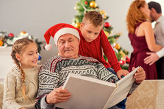 Mature man viewing photos with kids on holiday. Old grandfather is showing album of photographs to his grandchildren. Boy and girl is sitting on couch and stock image