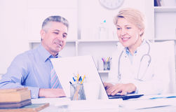 Mature man visits doctor. Mature men comes to doctor in clinic for advice on health royalty free stock images
