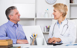 Mature man visits doctor. Mature men visits doctor in hospital for consultation on health and treatment royalty free stock photos