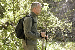 A mature man walking outdoors, holding walking poles and carrying a rucksack Stock Images