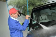 Mature man washing car with pressured water. Mature man washing a car with pressured water Royalty Free Stock Images