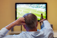 Mature man watching football on TV Royalty Free Stock Image