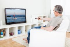 Mature man watching tv Stock Photography