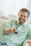 Mature Man Watching TV On Sofa Royalty Free Stock Photo