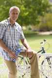 Mature man with water bottle on fence by bicycle, smiling, portrait Stock Image