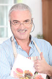 Mature man wearing apron Stock Images