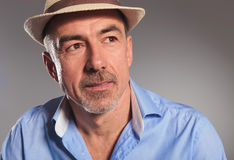 Mature man wearing blue open shirt and brown hat Stock Image
