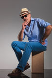Mature man wearing hat and sunglasses while thinking Stock Photography