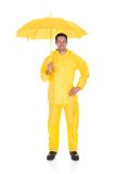 Mature man wearing raincoat and holding umbrella over white background Royalty Free Stock Photo