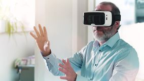 Mature man wearing virtual reality googles / VR Glasses stock video footage