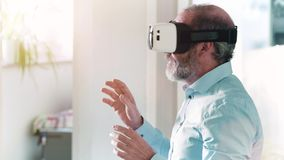 Mature man wearing virtual reality googles / VR Glasses stock footage