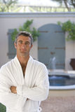 Mature man wearing white bath robe, arms crossed, smiling, portrait, fountain in background Stock Photography
