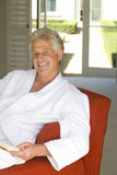 Mature man wearing white bath robe, sitting on with book on sofa, smiling, portrait Stock Photos
