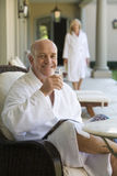 Mature man wearing white bath robe, sitting in deck chair with glass of water, smiling, portrait, woman standing in background Royalty Free Stock Photos