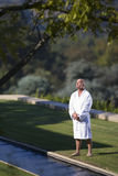 Mature man wearing white bath robe standing on lawn, eyes closed, elevated view Royalty Free Stock Images