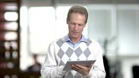 Mature man web surfing on pc tablet. Caucasian middle-aged manager working on digital tablet, blurred background stock video