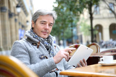 Mature man websurfing on tablet in coffee shop royalty free stock photo