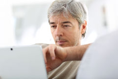 Mature man websurfing on tablet Royalty Free Stock Image