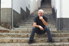 Mature man with white hair sitting on urban steps. Mature man sitting on steps in the street. Senior male with white hair and beard wearing casual clothes in Royalty Free Stock Images