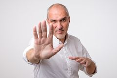 Mature man in yellow shirt showing sign stop with hand. Mature man in white shirt showing sign stop with hand. Deny to do something royalty free stock photography