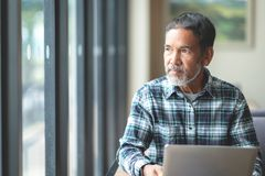 Mature man with white stylish short beard looking outside window. Casual lifestyle of retired hispanic people royalty free stock images