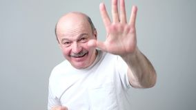 Mature man in white t-shirt shows five fingers. Studio shot stock footage