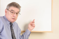 Mature man at whiteboard Stock Images