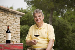 Mature Man and Wine. A mature man holding a glass of red wine royalty free stock photos