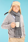 Mature man in winter clothes holding a cup of tea Stock Images