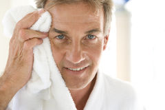 Mature man wiping face with towel, smiling, portrait, close-up Royalty Free Stock Photos