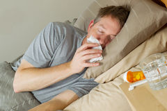 Mature Man wipiung Nose while lying in bed. Closeup photo of mature man wiping nose with tissue while lying in bed with night stand and medicine in forefront royalty free stock images