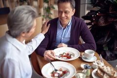 Mature man and woman enjoying together in cafe. Enjoyable meetings. Waist up top angle portrait of happy aged gentleman having dinner in cafe with lady while she royalty free stock images