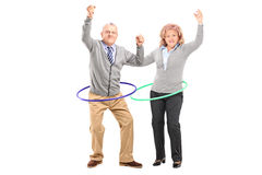 Mature man and woman exercising with hula hoop Royalty Free Stock Photography