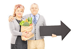 Mature man and woman holding a bag and big black arrow pointing Royalty Free Stock Photo
