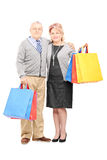 Mature man and woman holding shopping bags and looking at camera Stock Photo