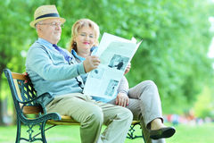 Mature man and woman reading the news outdoor. Mature men and women reading the news outdoors Royalty Free Stock Photo