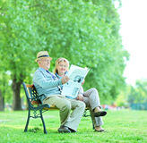 Mature man and woman reading the news outdoors Stock Photo