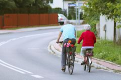 Mature man and woman rides a bicycle among the greens. A healthy and active part of life. Ecological transport for the population. Free time for retirement royalty free stock photos